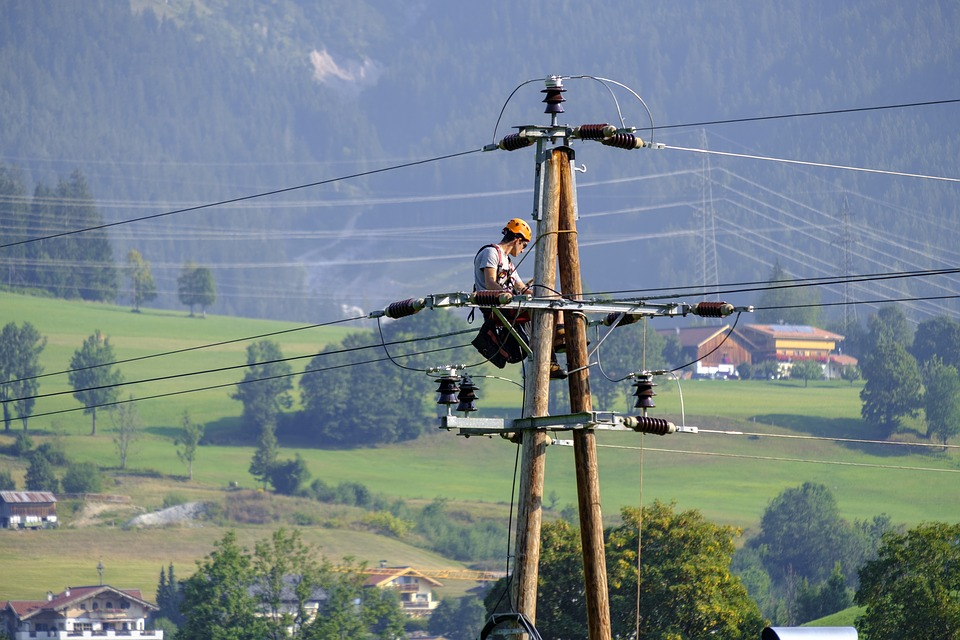 Электрик на столбе ремонтирует ЛЭП